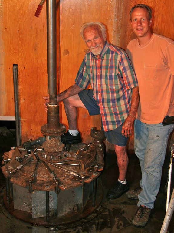 Description of . Former owner Charles Posey and his son-in-law, current owner Mike Titus, repair the water-powered turbine at Yates Cider Mill in 2010. (Photos courtesy of Yates Cider Mill)