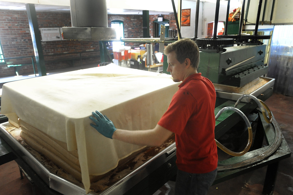 . Matthew Elenbaas works the cider press at Yates Cider Mill. (The Macomb Daily/DAVID DALTON)